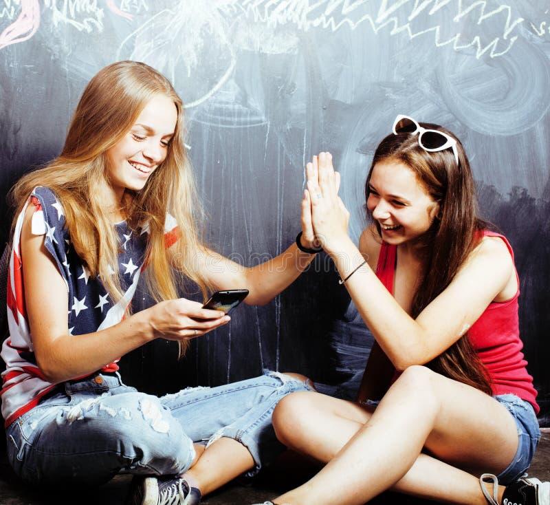 Di nuovo alla scuola dopo le vacanze estive, due ragazze reali teenager in aula con la lavagna dipinta insieme, stile di vita fotografia stock libera da diritti