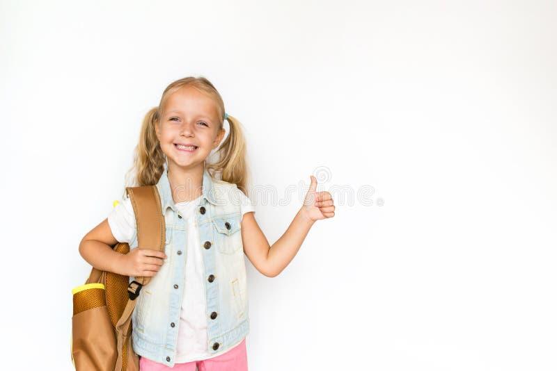 Di nuovo alla scuola ed al tempo felice Bambino sveglio con capelli biondi su fondo bianco Bambino con lo zaino Ragazza pronta a  immagini stock libere da diritti