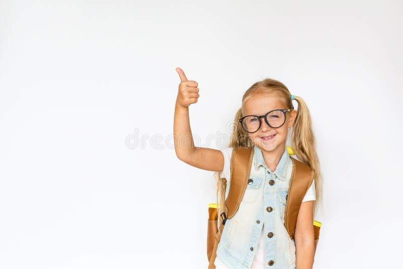 Di nuovo alla scuola ed al tempo felice Bambino sveglio con capelli biondi su fondo bianco Bambino con lo zaino Ragazza pronta a  fotografie stock