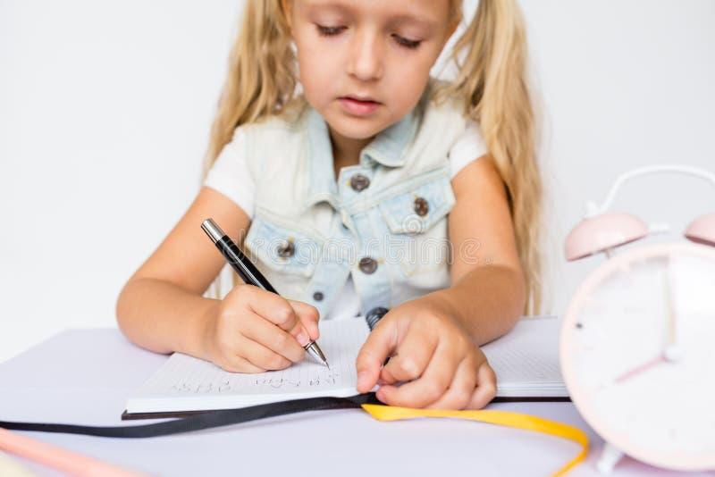 Di nuovo alla scuola ed al tempo felice Penna di tenuta dei bambini e scrivere in taccuino sul fondo bianco Bambino che fa compit immagini stock