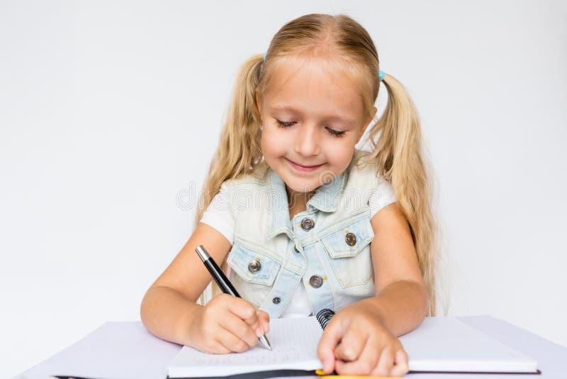 Di nuovo alla scuola ed al tempo felice Penna di tenuta dei bambini e scrivere in taccuino sul fondo bianco Bambino che fa compit immagine stock