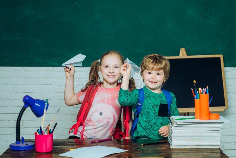 Di nuovo alla scuola ed al tempo felice Ragazzo abile sveglio felice e bambina sveglia con l'aeroplano di carta del giocattolo Pr fotografia stock