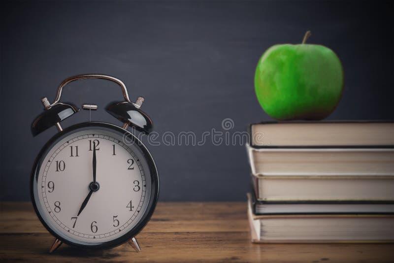 Di nuovo alla scuola, la vecchia sveglia d'annata vicino ai libri impilati contro la lavagna e la mela fruttificano immagine stock