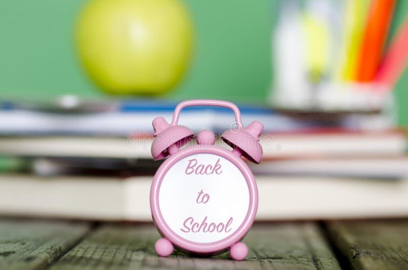 Di nuovo alla scuola scritta con il rosa sul piccolo orologio con il mucchio del fischio immagini stock libere da diritti