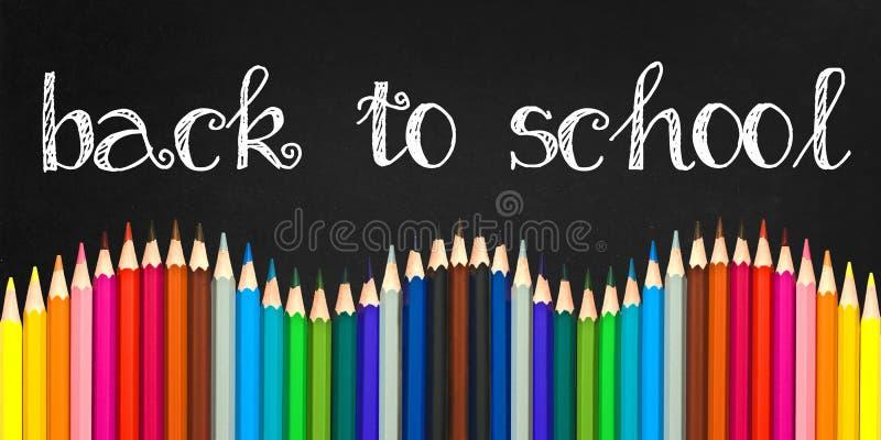 Di nuovo alla scuola scritta su un fondo della lavagna con un'ondata di matite di legno variopinte fotografia stock libera da diritti