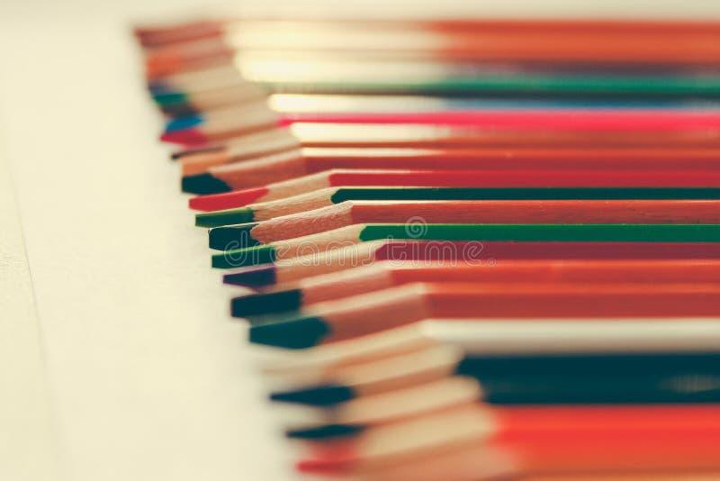 Di nuovo a scuola, concetto dalle matite colorate su un fondo giallo da carta strutturata per schizzare Tinto in un d'avanguardia immagine stock