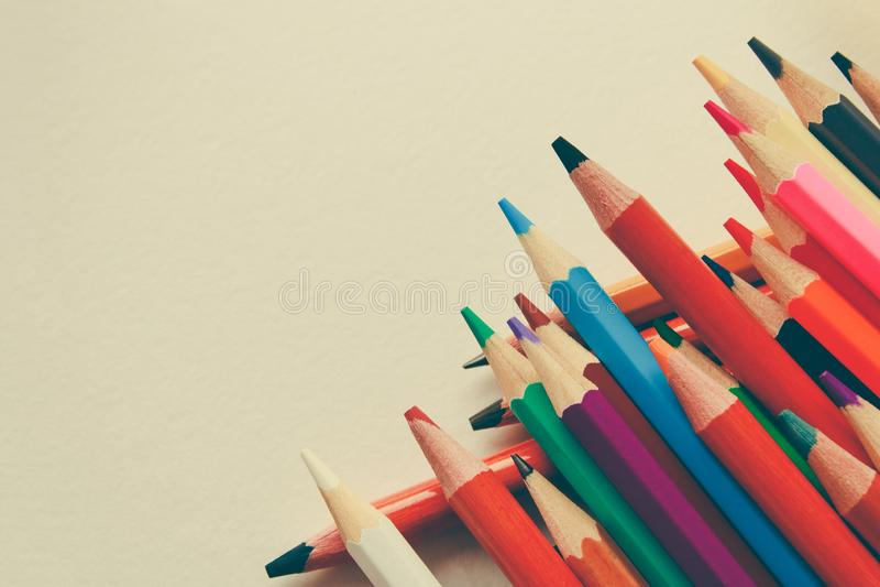 Di nuovo a scuola, concetto dalle matite colorate su un fondo giallo da carta strutturata per schizzare Tinto in un d'avanguardia immagine stock libera da diritti