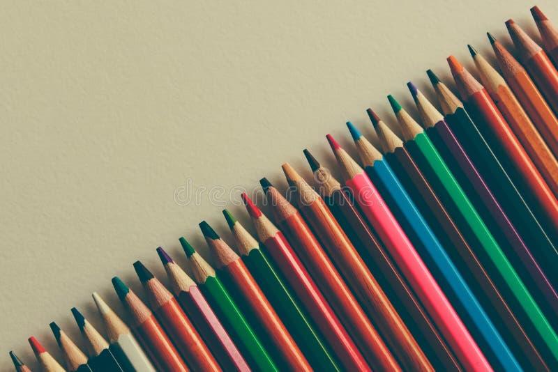 Di nuovo a scuola, concetto dalle matite colorate su un fondo giallo da carta strutturata per schizzare Tinto in un d'avanguardia fotografia stock libera da diritti
