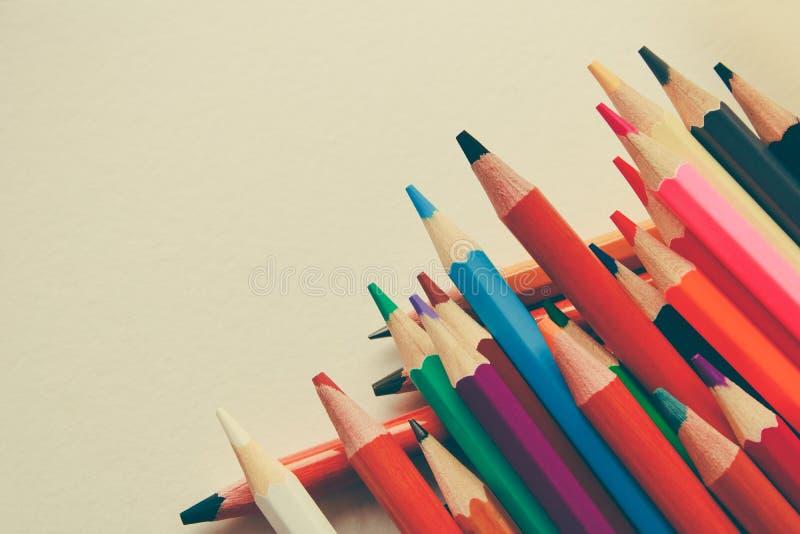 Di nuovo a scuola, concetto dalle matite colorate su un fondo giallo da carta strutturata per schizzare Tinto in un d'avanguardia fotografie stock