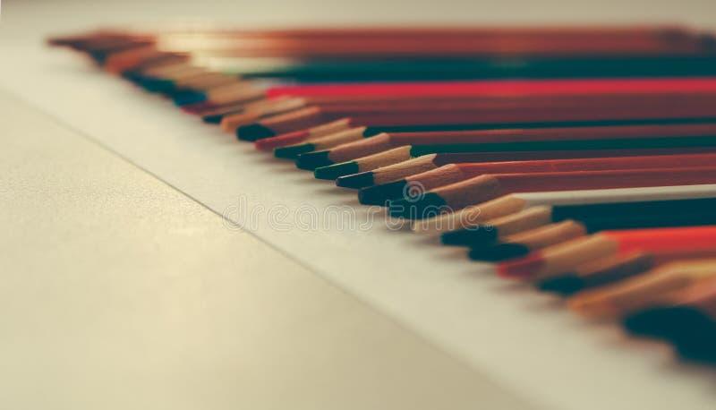 Di nuovo a scuola, concetto dalle matite colorate su un fondo giallo da carta strutturata per schizzare Tinto in un d'avanguardia fotografia stock