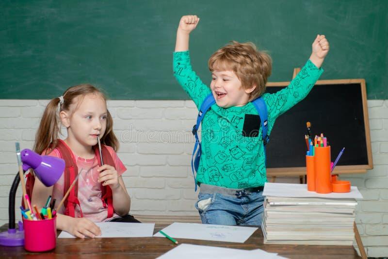 Di nuovo a scuola - concetto di istruzione Ragazzo abile sveglio felice e bambina sveglia con il libro Ragazzino sorridente alleg immagini stock libere da diritti