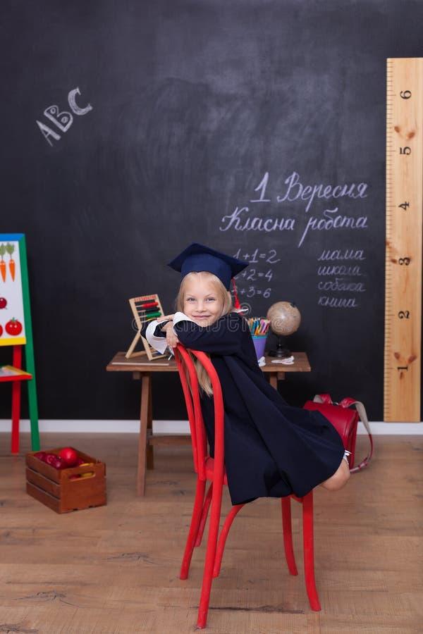 Di nuovo a scuola! La bambina allegra sta sedendosi sulla lezione Esaminando la macchina fotografica Concetto del banco La ragazz immagine stock