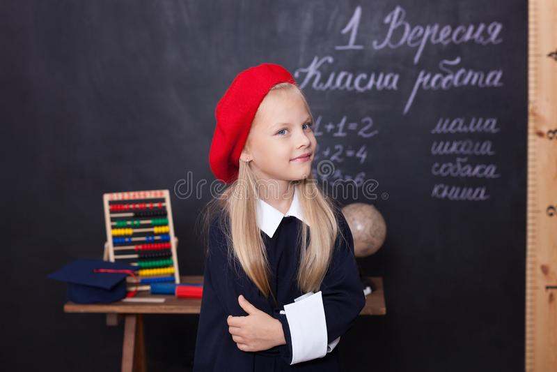 Di nuovo a scuola! Una scolara sta alla lavagna con un righello Una scolara risponde alla lezione Un primo selezionatore vicino a fotografia stock