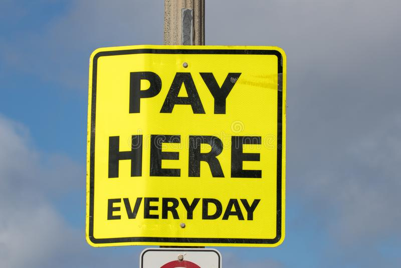 Di paga segno giallo di ogni giorno qui fotografia stock libera da diritti