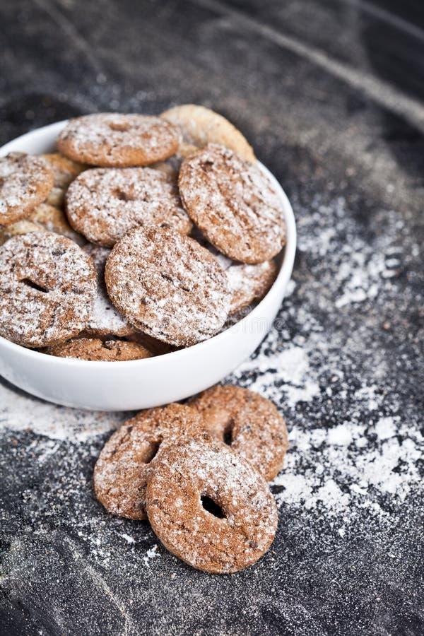 Di pepita di cioccolato al forno fresco e biscotti freschi dell'avena con il mucchio della polvere dello zucchero in ciotola bian fotografia stock libera da diritti