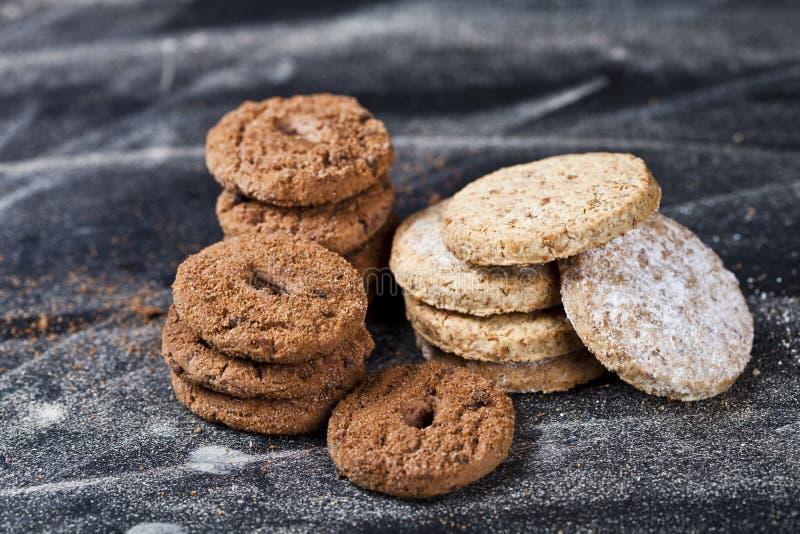 Di pepita di cioccolato e biscotti freschi dell'avena con le pile della polvere dello zucchero fotografia stock