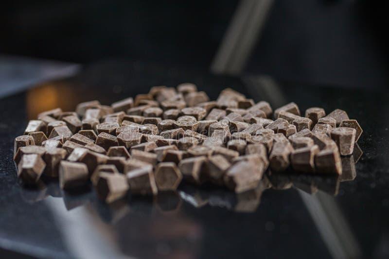 Di pepita di cioccolato, pezzi del cioccolato per produrre i dessert, glassa, isolata sulla vista laterale del fondo nero fotografie stock libere da diritti
