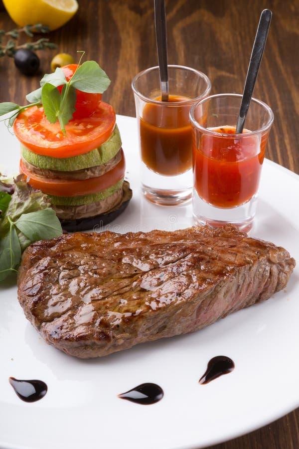 Di recente bistecca arrostita succosa servita con la salsa e le verdure di peperoncino rosso immagine stock libera da diritti