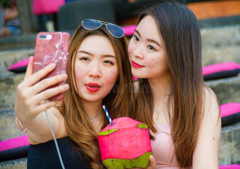 Di stile di vita ritratto all'aperto di giovani ragazze cinesi asiatiche felici e belle che prendono l'immagine del selfie con il fotografia stock libera da diritti