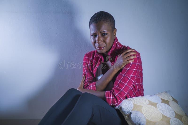 Di stile di vita ritratto all'interno di giovane donna americana dell'africano nero triste e depresso che si siede a casa sensibi immagine stock libera da diritti