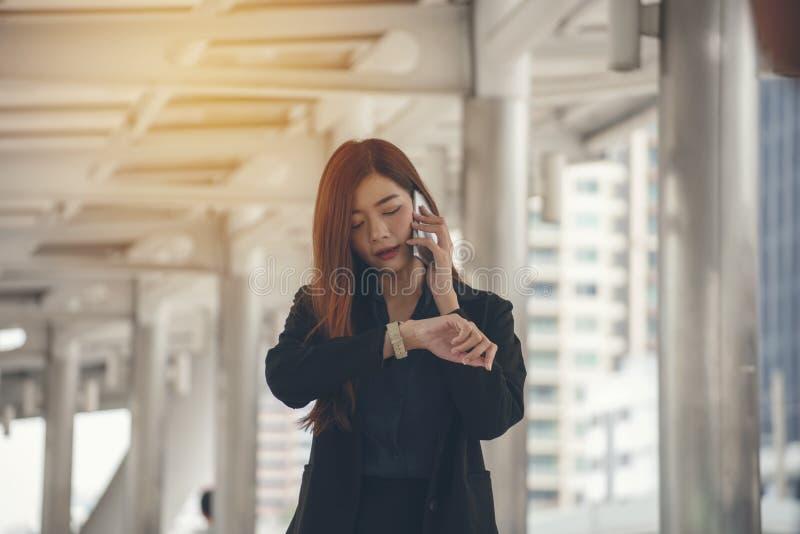 Di tempo concetto fuori Lavoro urgente, donna di affari che vede orologio e che per mezzo del telefono cellulare prima della riun fotografia stock