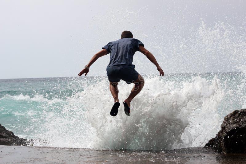 31/5000 di uomo volny del vsplesk del prygayet v di muzhchina che salta in una spruzzata dell'onda fotografia stock