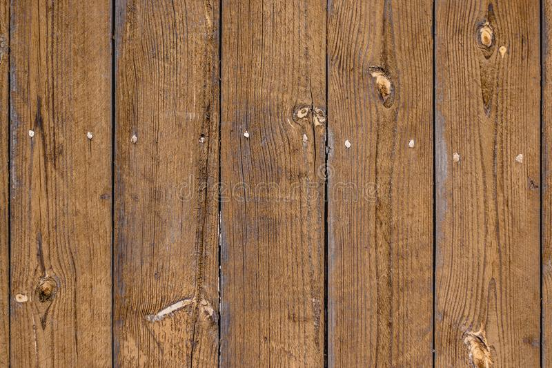 Di vecchio recinto con i bordi verticali, colore sbiadito marrone chiaro, nodi sui bordi del pino fotografia stock