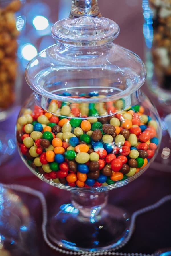 Di vetro in pieno delle gocce di cioccolato colorate fotografia stock