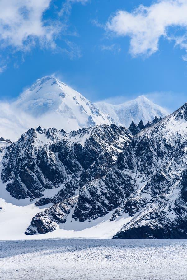 Dia bonito do céu azul com picos de montanha cobertos de neve, e vento que funde o fundo da neve, o branco e o azul da natureza, fotos de stock