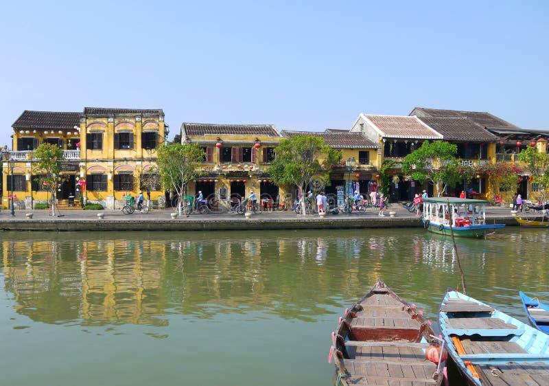 Dia bonito na cidade antiga de Hoi An com opinião barcos tradicionais, casas amarelas e turistas imagem de stock royalty free