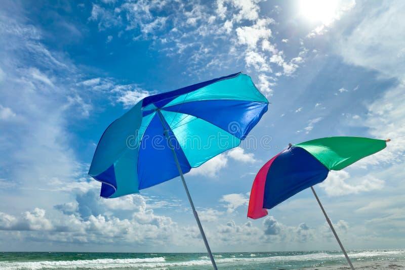 Dia brilhante na praia com guarda-chuvas fotografia de stock royalty free