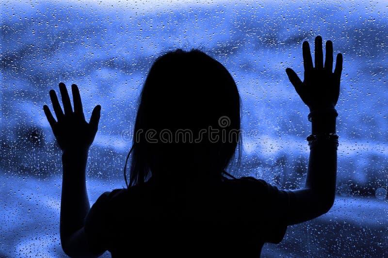 Dia chuvoso com a menina na janela que olha para fora imagens de stock