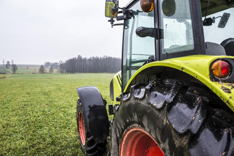 Dia chuvoso no outono atrasado Trator na borda de um prado com grama verde imagem de stock royalty free
