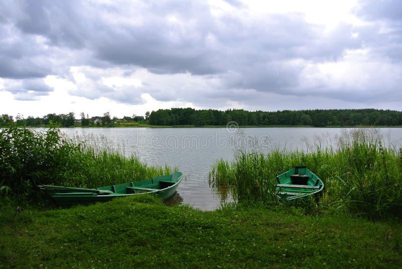 Dia chuvoso no parque natural de Trakai, uma vista a um lago, floresta e barcos de pesca verdes fotografia de stock