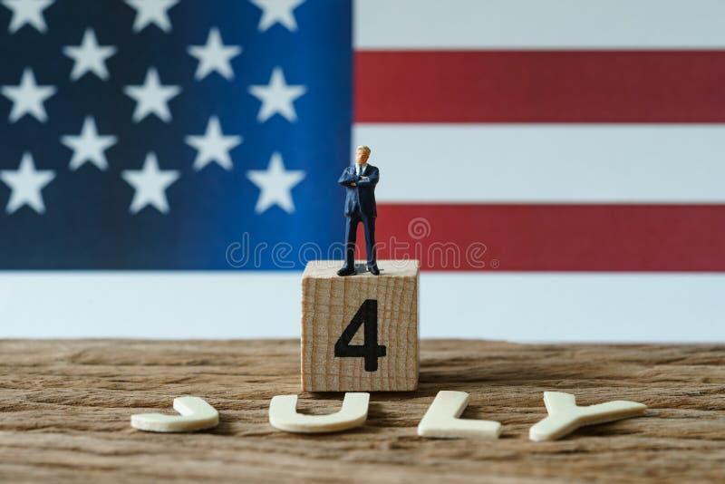 Dia da Independência EUA com figura diminuta posição do homem de negócios fotografia de stock royalty free