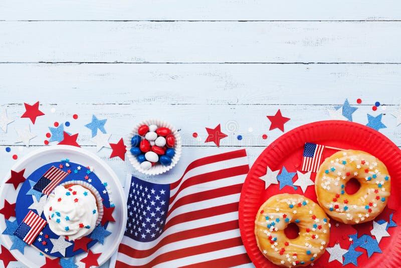 Dia da Independência fundo feliz do 4 de julho com bandeira americana e os alimentos doces, decorados com estrelas e confetes Vis imagem de stock royalty free