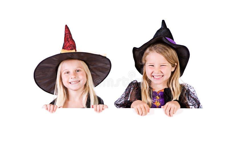 Dia das Bruxas: Bruxas bonitos que olham sobre o cartão branco imagens de stock royalty free