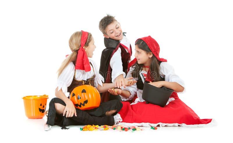 Dia das Bruxas: Crianças que compartilham de doces de Dia das Bruxas fotos de stock royalty free