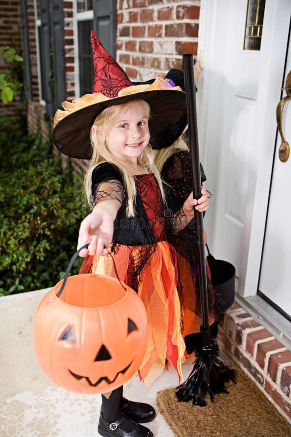 Dia das Bruxas: Bruxas da menina na campainha de soada do patamar foto de stock