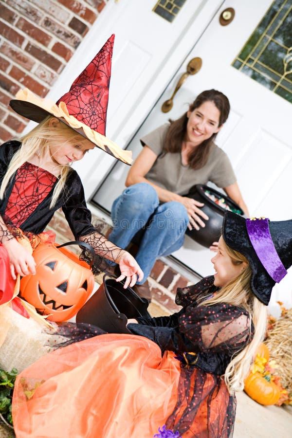 Dia das Bruxas: Doces de Sit On Front Porch Checking das meninas imagem de stock
