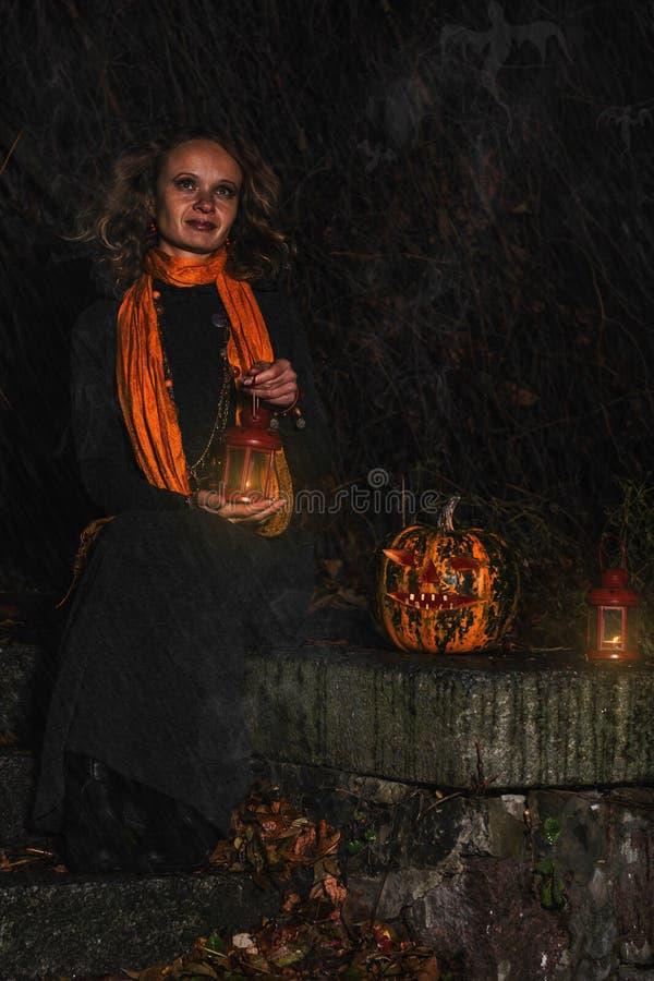 Dia das Bruxas feliz! Uma bruxa bonita com uma abóbora grande Yo bonito fotos de stock