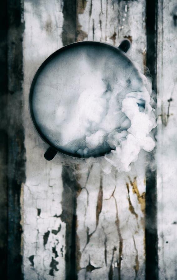 Dia das Bruxas: O caldeirão da bruxa aérea enchido com a poção mágica imagem de stock