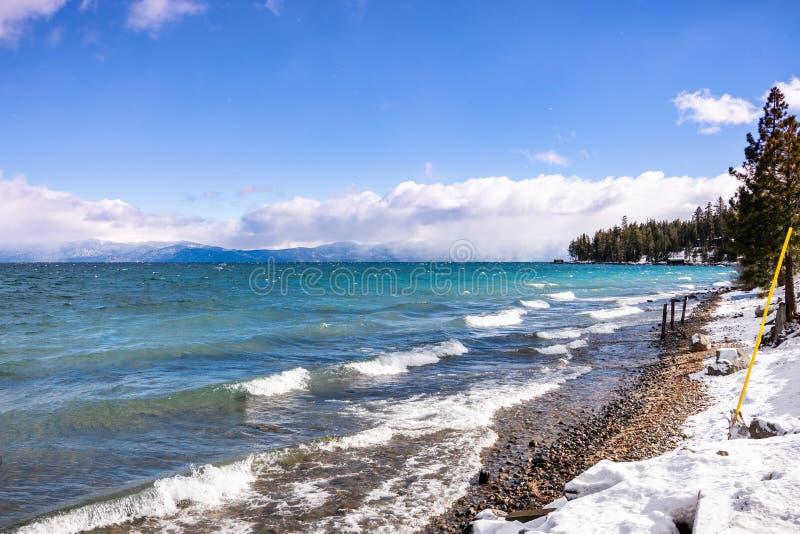 Dia de inverno ensolarado na linha costeira de Lake Tahoe, serra montanhas, Califórnia; quebrando a ressaca criada pelo vento que fotos de stock royalty free