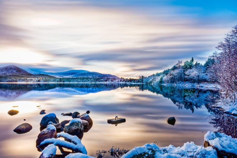 Dia de invernos bonito com nuvens macias, neve em árvores e rochas, reflexões na água calma no Loch Morlich imagem de stock