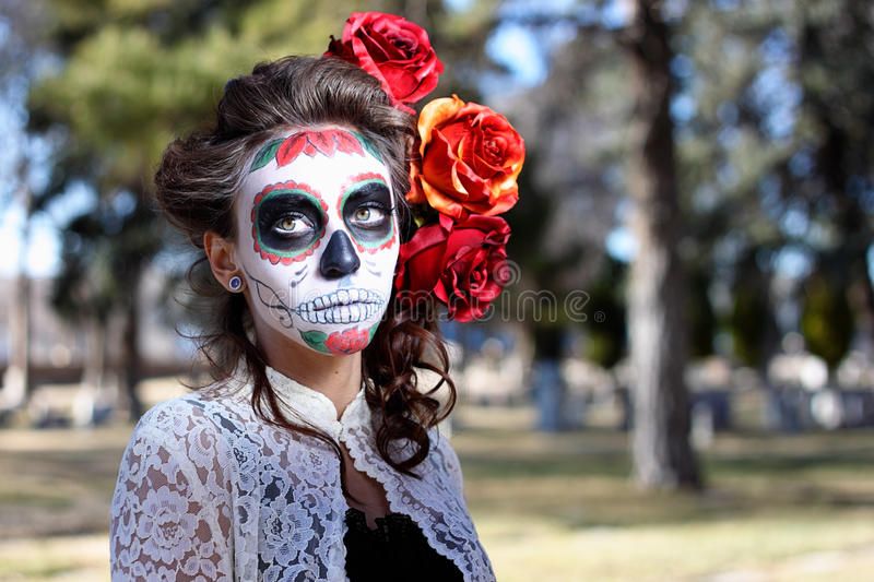 Dia De Los Muertos. Woman in Dia De Los Muertos, Day of the Dead, makeup in cemetary stock photo
