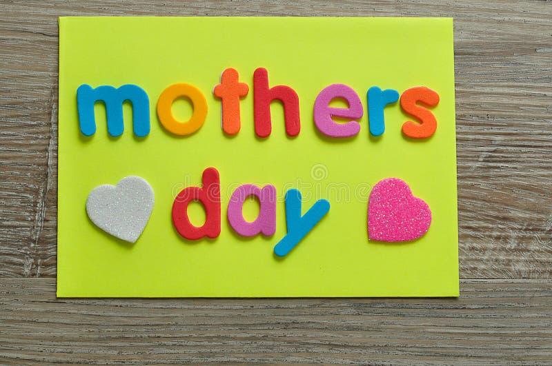 Dia de mães em uma nota amarela com um coração branco e cor-de-rosa imagens de stock