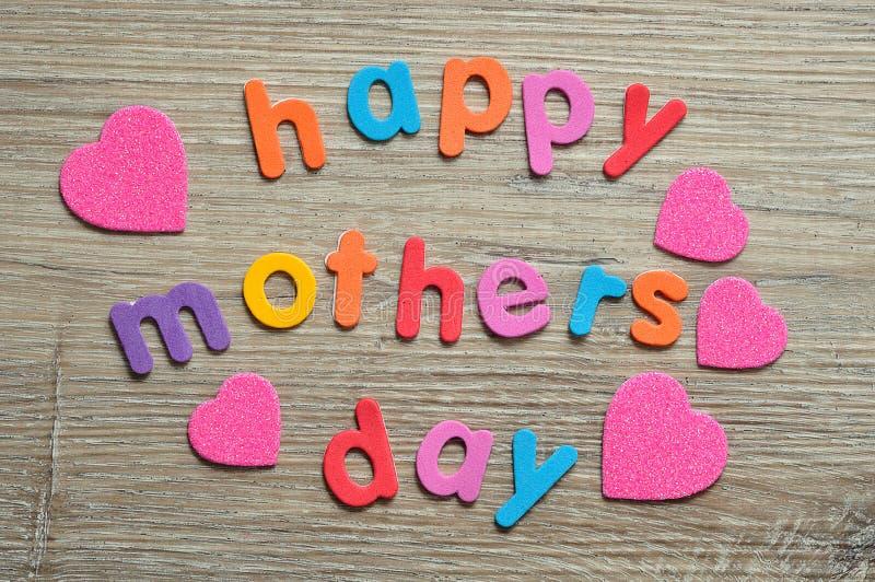 Dia de mães feliz em letras coloridas com corações cor-de-rosa fotografia de stock