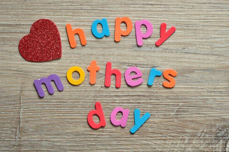 Dia de mães feliz em letras coloridas com um coração vermelho fotografia de stock royalty free