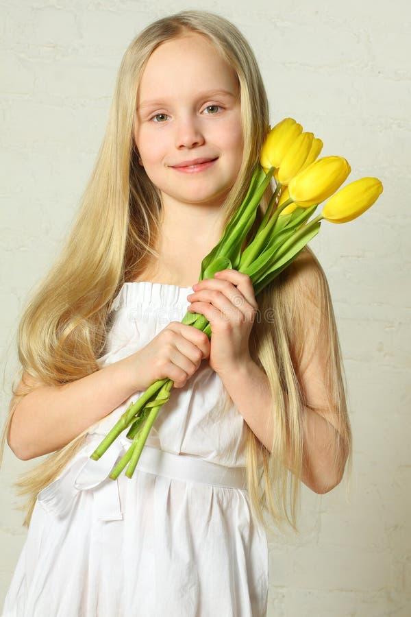 Dia de matriz - criança bonito com tulips das flores foto de stock