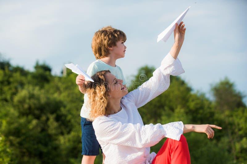 Dia de matrizes Criança feliz que mostra seu avião de papel do pai Adote a crian?a Liberdade para sonhar - o menino alegre que jo imagem de stock